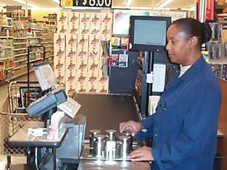 Picture of inspector checking a weighing device in a grocery store.