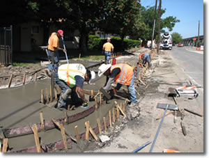 Photo of men building a sidewalk.