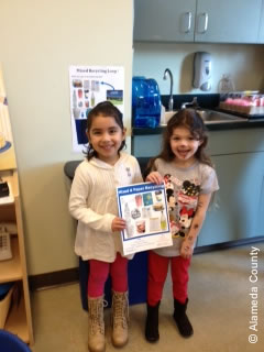 Photo of preschoolers holding up recycling guide.