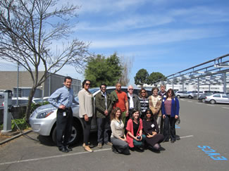 Photo of green ambassadors in front of an electric car.