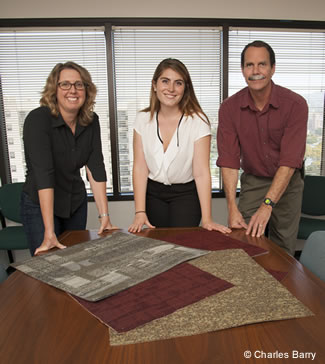 Photo of employees looking over carpet samples.