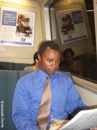 Photo shows County employee reading a newspaper while riding BART to work.