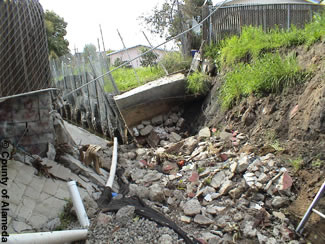 Photo shows Peralta Creek before. Shows deteriorating concrete flood channels, debris and trash accumulation.