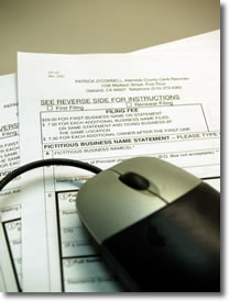Photo of a computer mouse on a stack of forms.