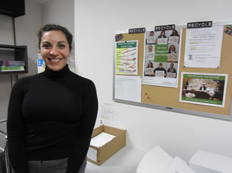 Photo of Green ambassador standing next to Recycle bulletin board.