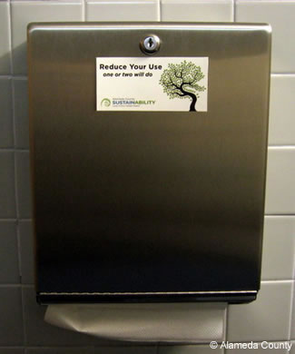 Photo of reduce use sticker on paper towel dispenser.