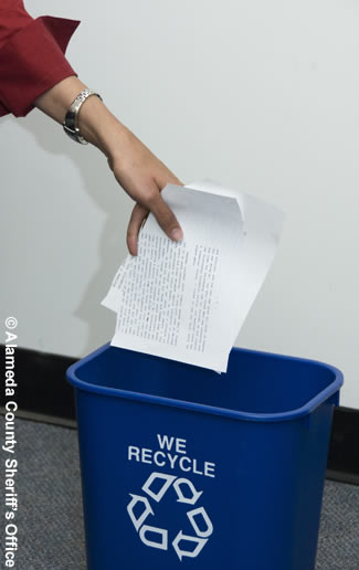 Photo of an employee putting papers in a recycle can.