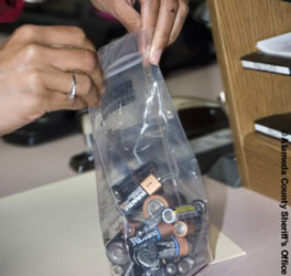 Photo of a County employee placing batteries into a recycling bag.