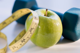 an apple, tape measure, and dumbbell weight
